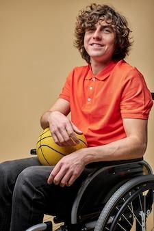 Ragazzo disabile di mentalità aperta che tiene palla da basket e sorridente, gli piace giocare a giochi sportivi, sogna di alzarsi in piedi più velocemente e non si arrende