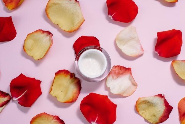 Crema idratante aperta con petali di rosa. il concetto di cura della pelle, cura anti-invecchiamento, ingredienti naturali nei cosmetici