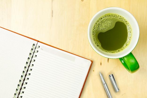 Apra il taccuino e la penna con greentea su fondo di legno. vista dall'alto, concetto di posa piatta.