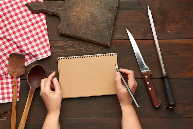 Apra il taccuino con fogli marroni vuoti e utensili da cucina