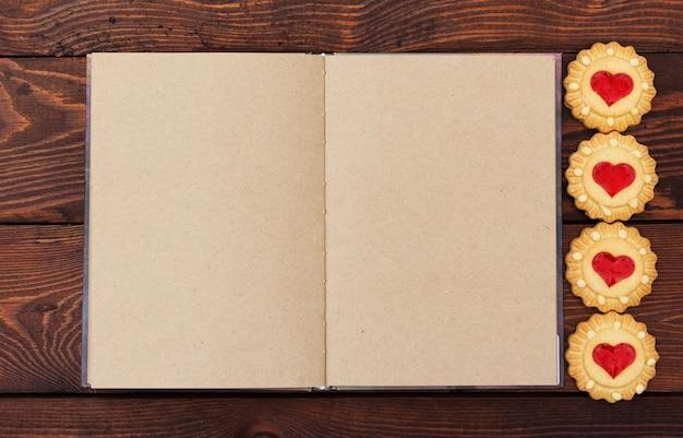 Apra il taccuino con le pagine in bianco su fondo di legno, biscotti a forma di cuore