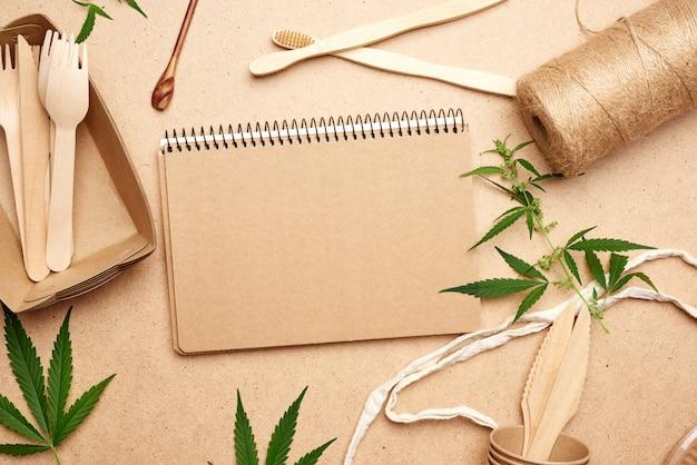 Taccuino aperto con fogli vuoti, una borsa in tessuto e stoviglie usa e getta in carta marrone artigianale, foglie di canapa verde