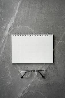 Apra il taccuino con gli occhiali sulla vista superiore del tavolo in marmo grigio, blocco note a spirale sul desktop dell'ufficio grigio. chiaro per fare la lista, piatto lay.