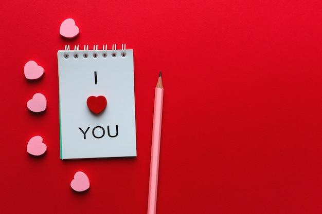Apra il taccuino con la scritta ti amo, cuori rosa, matita su rosso