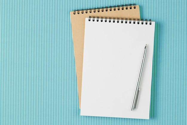 Apra il taccuino con la penna sulle pagine vuote. quaderno di scuola sulla parete verde, blocco note a spirale su un tavolo, piatto laici