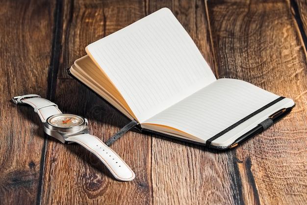 Apra il taccuino con la penna e l'orologio da polso sul tavolo