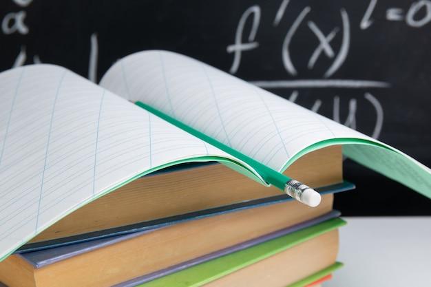 Apra il taccuino con matita e libri sul fondo della lavagna. concetto di educazione.