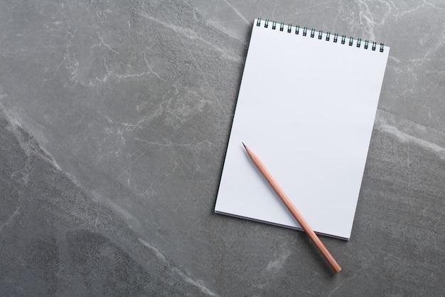 Apra il taccuino con la matita di legno sulla vista superiore della parete di marmo, il blocco note della scuola su un tavolo scuro, la disposizione piana della scrivania dell'ufficio