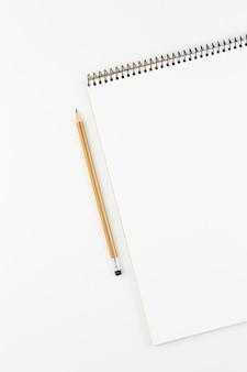 Apra il taccuino con la matita gialla sulla vista superiore del tavolo bianco, blocco note a spirale con la pagina in bianco. disposizione piana del concetto di ufficio, vista verticale