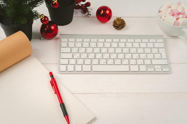 Blocco note aperto e computer sul tavolo con decorazioni natalizie