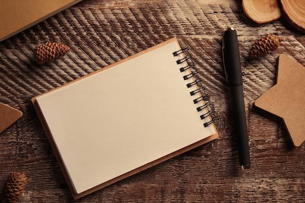Apra il blocco note e la penna su fondo di legno