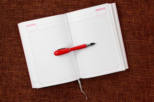 Apra il blocco note e il primo piano rosso della penna