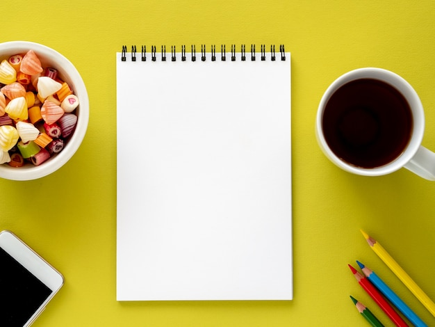 Aprire il blocco note a spirale con una pagina bianca pulita, una tazza con il tè, caramelle in una ciotola, una matita colorata