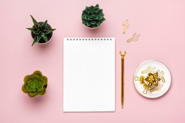 Penna dorata di succulente del blocco note aperto su taccuino a spirale di sfondo rosa sul tavolo edu...