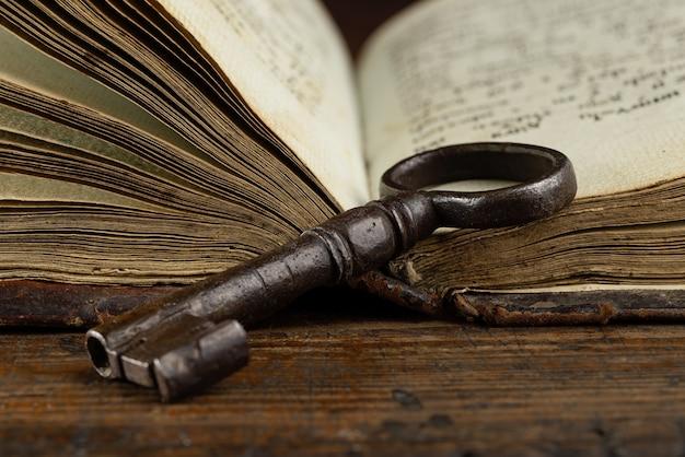 Un vecchio libro aperto su cui giace un primo piano di oggetti d'antiquariato con chiave in metallo
