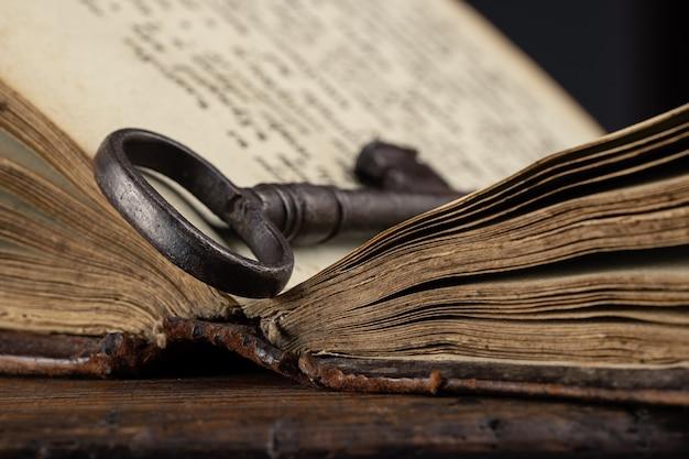 Un vecchio libro aperto su cui giace una chiave di metallo antiquariato