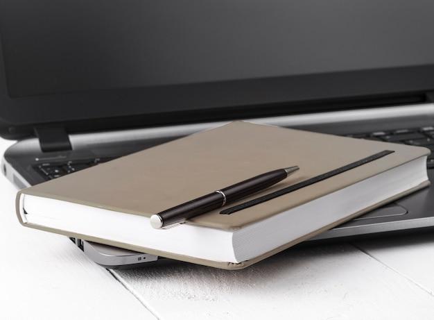 Apri il taccuino arancione con una matita sdraiata su un laptop tra sfondi di legno