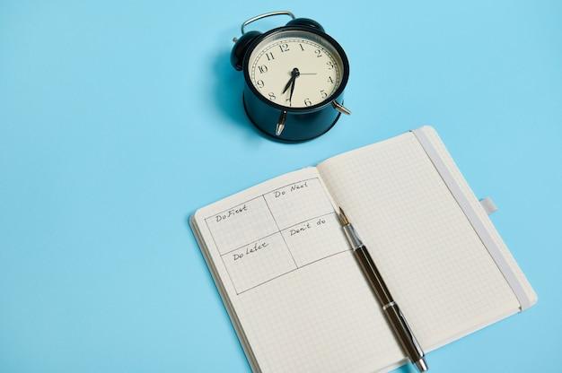 Un taccuino organizzatore aperto con orario del giorno per ora, penna, sveglia su sfondo colorato con spazio per le copie. gestione del tempo, scadenza e concetto di corretta pianificazione e organizzazione del tempo