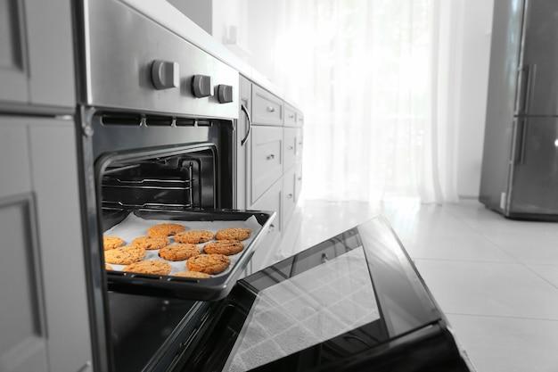 Forno aperto con gustosi biscotti fatti in casa in cucina