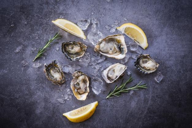 Apri guscio di ostrica con spezie alle erbe limone rosmarino servito da tavola e ghiaccio sano frutti di mare cena di ostriche cruda nel ristorante cibo gourmet - ostriche fresche frutti di mare sulla banda nera