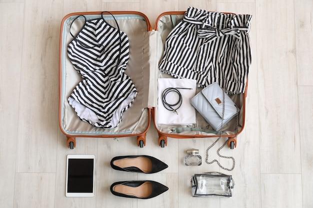 Apra la valigia e gli accessori imballati sulla tavola di legno