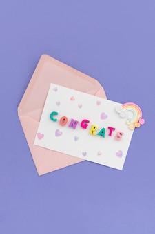 Aprire la busta rosa con la parola complimenti su sfondo viola.