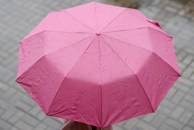 Un ombrello rosa aperto su cui cade la pioggia. scegliere un concetto di ombrello