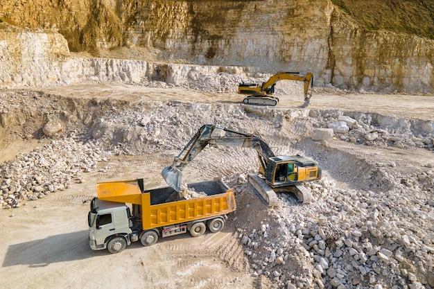 Estrazione a cielo aperto di materiali da costruzione in pietra arenaria con escavatori e dumper.