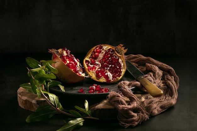 Aprire il melograno in un piatto con foglie su un tavolo scuro
