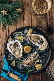 Ostriche crude aperte con limone e rosmarino. frutti di mare freschi su un vassoio di metallo su un fondo di legno rustico vista dall'alto. decorazioni natalizie
