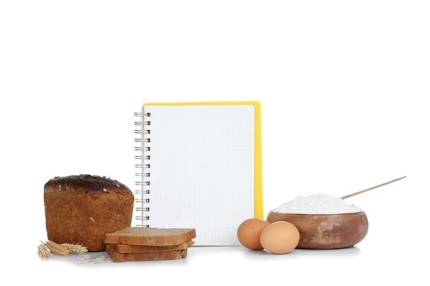Libro di ricette aperto e pane sulla parete bianca