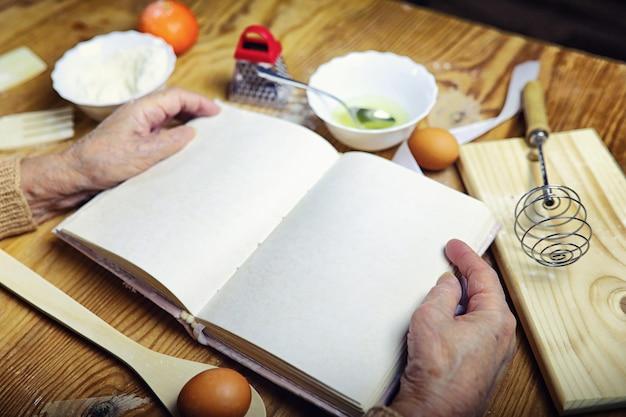 Aprire il ricettario nelle mani di una donna anziana davanti a un tavolo con utensili