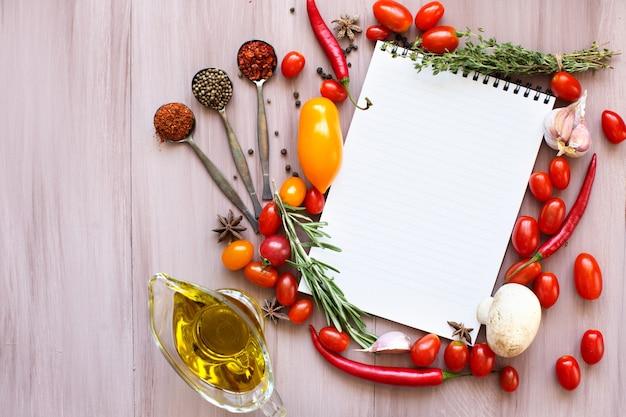 Libro di ricette aperto con erbe aromatiche, pomodori e spezie sulla tavola di legno