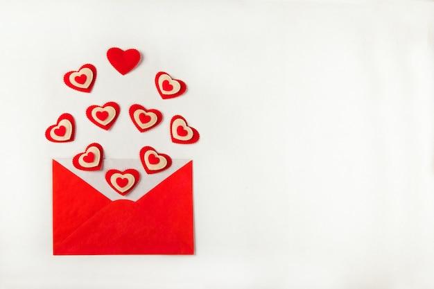 Apra la busta rossa con un sacco di cuori rossi diversi che escono e sparsi su uno sfondo bianco come lettera d'amore. concetto di san valentino. vista dall'alto, piatto laico