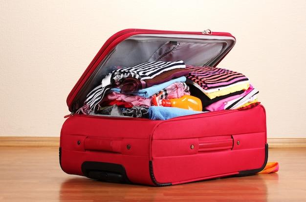 Apra la valigia rossa con i vestiti nella stanza