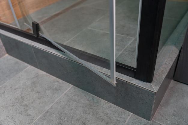 Aprire la porta girevole in vetro su un box doccia piastrellato in una vista a livello del pavimento ad angolo basso dell'angolo