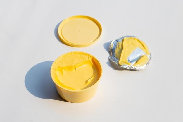 Aprire il contenitore rotondo con burro o margarina su sfondo bianco.