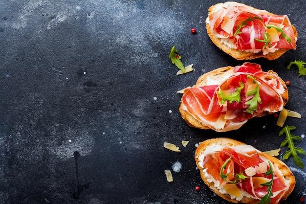 Aprire i panini con prosciutto, rucola e formaggio a pasta dura su una vecchia superficie scura di cemento