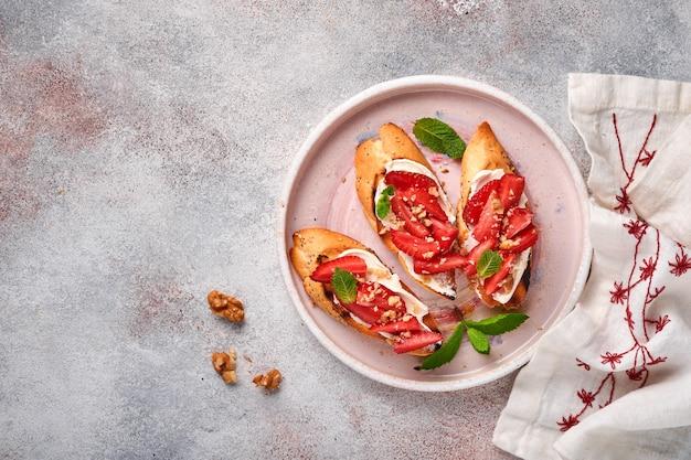 Panini aperti con fragole, formaggio morbido alla menta e noci in un piatto di ceramica su uno sfondo di pietra grigio chiaro. estate e cibo dietetico sano, concetto di cibo vegetariano. vista dall'alto.