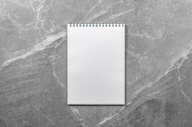Apra il taccuino di scuola sulla vista superiore del tavolo in marmo, blocco note con una pagina vuota. disposizione piatta del concetto di ufficio