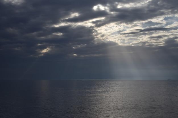 Mare aperto con nuvole e sole che filtra attraverso