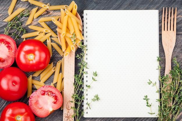 Libro di cucina foglio aperto con motivo a pois, cucchiaio con pasta di penne, pomodori, timo su fondo di legno vecchio
