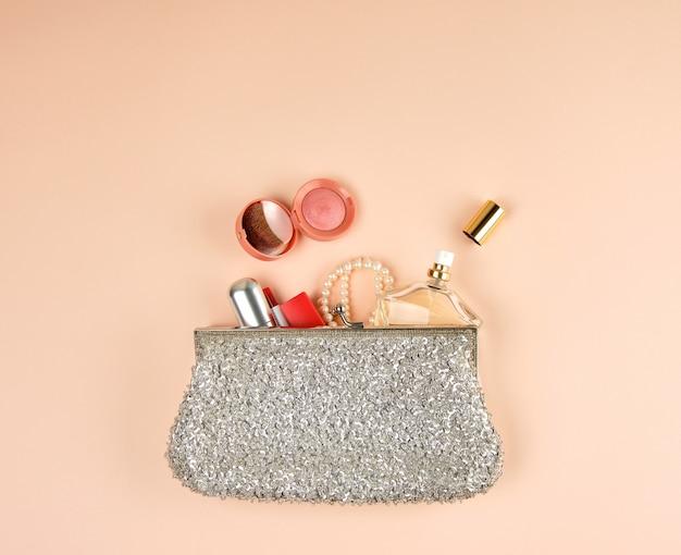 La clutch aperta d'argento e i cosmetici sono caduti dal centro