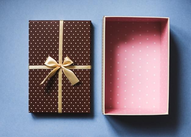 Aprire la confezione regalo elegante sul concetto di vacanze sfondo blu. vista dall'alto.
