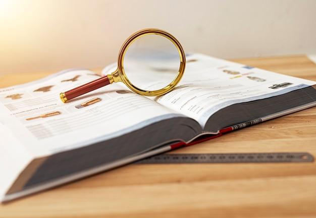 Libro tecnico aperto per lo studio della fisica con lente d'ingrandimento e righello.