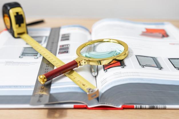 Libro tecnico aperto con lente di ingrandimento e metro a nastro sulla scrivania in legno da vicino.
