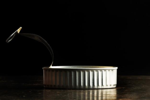 Un barattolo di latta aperto su uno sfondo scuro