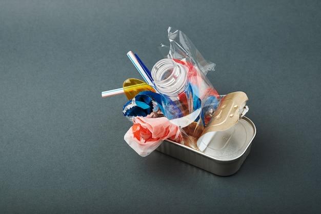 Barattolo di latta aperto. rifiuti di plastica invece di pesce all'interno. concetto di inquinamento da plastica dell'oceano