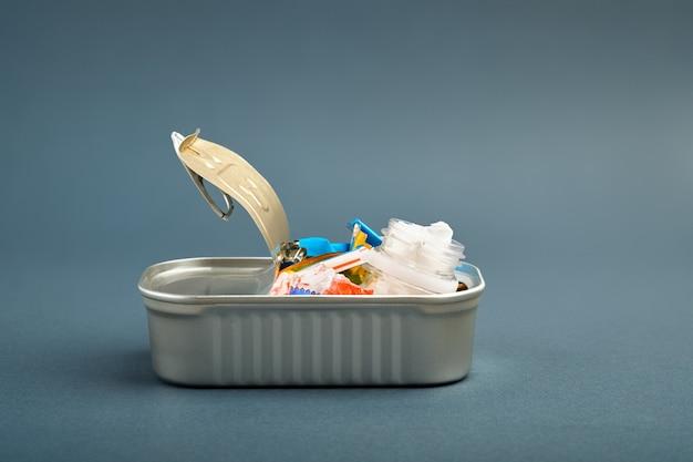 Barattolo di latta aperto. rifiuti di plastica al posto del pesce dentro. concetto di inquinamento di plastica dell'oceano