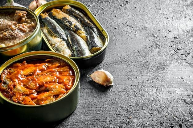 Aprire le lattine con pesce in scatola e carne sul tavolo rustico nero